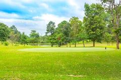 Campo de golfe bonito em azul-céu e em nuvem foto de stock