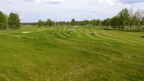 Campo de golfe da vista aérea Jogadores de golfe que andam abaixo do fairway em um curso com saco e trole de golfe Imagens de Stock