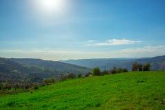 Campo de hierba verde en las pequeñas colinas y el cielo azul con las nubes fotografía de archivo libre de regalías