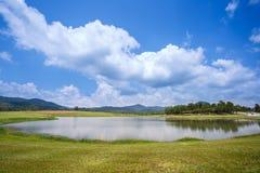 Campo de hierba y pequeño lago con el cielo nublado y azul encima en el parque de Singha imagen de archivo