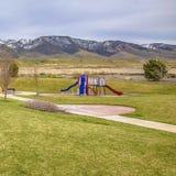 Campo de jogos colorido do quadrado do quadro no meio de um terreno gramíneo vibrante no dia ensolarado imagens de stock