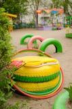 Campo de jogos da areia com um curso de obstáculo de pneus do trajeto com raquetes e instrutores de badminton no primeiro plano foto de stock royalty free