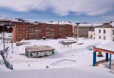Campo de jogos do ` s das crianças, coberto com a neve, na frente da casa foto de stock