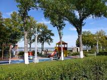 Campo de jogos do ` s das crianças na máscara de árvores verdes Imagens de Stock