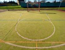 Campo de jogos exterior vazio do handball, superfície peludo plástica do verde na terra e linhas azuis brancas dos limites imagem de stock