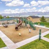 Campo de jogos quadrado do quadro e área de piquenique com casas e o lago bonitos no fundo fotografia de stock royalty free