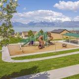 Campo de jogos quadrado do quadro e área de piquenique com lago e montanha das casas no fundo imagem de stock