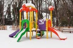 Campo de jogos vazio das crianças da neve no parque no tempo de inverno imagens de stock