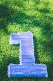 Campo de la hierba, una figura que miente en la hierba, el cumpleaños del primer año de vida Imagen de archivo