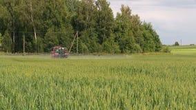 Campo de la planta cultivada del verano de la agricultura del espray del tractor de granja almacen de metraje de vídeo