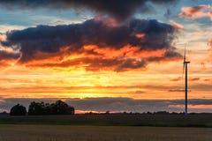 Campo de la puesta del sol y de trigo con el molino de viento en fondo Nubes del rojo de Buning Foto de archivo