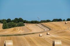 Campo de milho segado com os pacotes de feno redondos grandes - turbina eólica no fundo fotos de stock royalty free