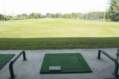 Campo de prácticas del campo de golf, pelota de golf lista para la impulsión en la conducción de r Foto de archivo