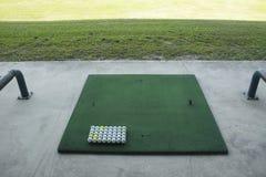 Campo de prácticas del campo de golf, pelota de golf lista para la impulsión en la conducción de r Imágenes de archivo libres de regalías