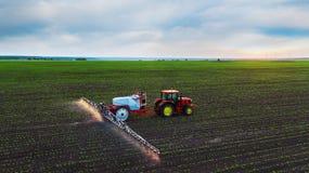 Campo de rociadura del tractor en la primavera Fotos de archivo