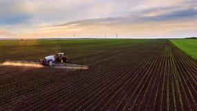 Campo de rociadura del tractor en la primavera Fotografía de archivo