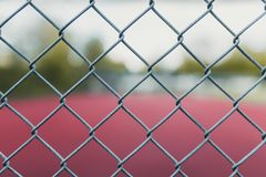 Campo de tênis obscuro com foco em uma cerca imagens de stock