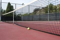 Campo de tenis con la pelota de tenis por la red Imagen de archivo