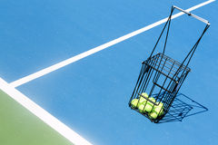 Campo de tenis con una cesta de la bola y pelotas de tenis en ella Fotos de archivo libres de regalías