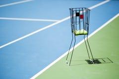 Campo de tenis con una cesta de la bola y pelotas de tenis en ella Imagen de archivo