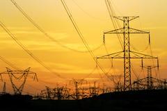 Campo de torres de alta tensão sob o céu dramático Foto de Stock Royalty Free