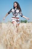 Campo de trigo hermoso de la mujer en día de verano asoleado. Fotos de archivo libres de regalías