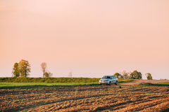 Campo de Volkswagen Polo Car Parking On Wheat Céu do nascer do sol do por do sol Fotografia de Stock