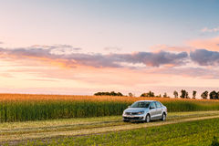 Campo de Volkswagen Polo Car Parking On Wheat Céu dramático do nascer do sol do por do sol Imagem de Stock
