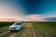 Campo de Volkswagen Polo Car Parking On Wheat Céu dramático do nascer do sol do por do sol Imagem de Stock Royalty Free