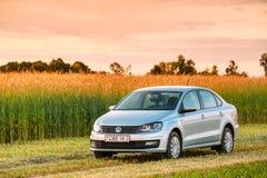Campo de Volkswagen Polo Car Parking On Wheat Céu dramático do nascer do sol do por do sol Fotografia de Stock