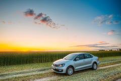 Campo de Volkswagen Polo Car Parking On Wheat Drama do nascer do sol do por do sol Foto de Stock Royalty Free