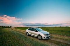 Campo de Volkswagen Polo Car Parking On Wheat Nascer do sol do por do sol dramático Fotografia de Stock