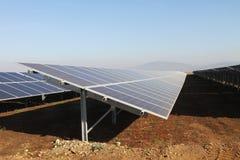 Campo dei pannelli solari fotovoltaici di energia verde Immagine Stock