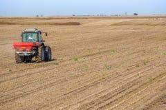 Campo dei residui della soia di fertilizzazione dell'agricoltore Immagini Stock