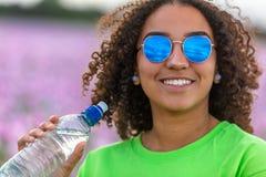 Campo del adolescente de la muchacha de la mujer de las flores que llevan las gafas de sol que beben la botella de agua imagenes de archivo