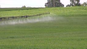 Campo del espray del tractor con el pesticida químico en verano metrajes