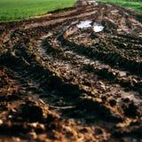 Campo del fango de la pista del tractor que cultiva la ecología Foto de archivo libre de regalías