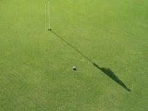 Campo del golf con el indicador y la bola Fotografía de archivo