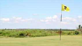 Campo del golf con la bandera amarilla almacen de video