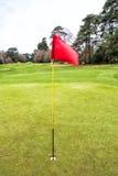 Campo del golf con la bandera roja Imágenes de archivo libres de regalías