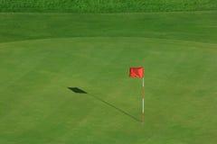Campo del golf con la bandera roja Imagenes de archivo