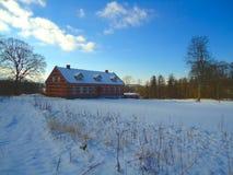 Campo del invierno con la casa y la nieve Imagen de archivo libre de regalías