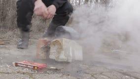 Campo del jugador de bolos, cocinando en un fuego, hombre que se calienta las manos sobre un fuego HD almacen de video