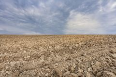 Campo del terreno coltivabile del suolo di agricoltura e fondo vuoti del cielo delle nuvole Immagine Stock