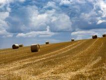 Campo del verano con las balas de heno debajo de las nubes de tormenta Agricultura concentrada Fotos de archivo