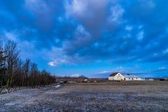 Campo dell'azienda agricola in Islanda con le costruzioni nella distanza Immagine Stock