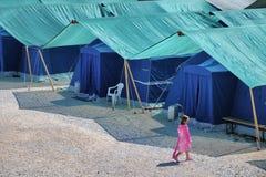 Campo della tenda dei rifugiati di terremoto con la camminata sola del bambino immagine stock