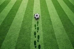 Campo di calcio con le stampe della scarpa e del pallone da calcio Immagini Stock Libere da Diritti