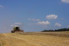 Campo di cereale dorato con la mietitrice Fotografie Stock Libere da Diritti