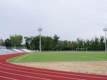 Campo di football americano verde e pista corrente rossa nello stadio Pista corrente su un fondo dello stadio Concetto di sport c Fotografia Stock Libera da Diritti